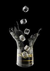 Splashing juice in glass. Isolated on black background