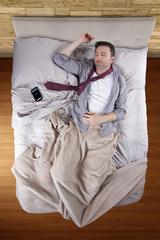 businessman sleeping with cellphone alarm clock