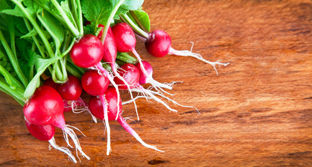bunch of radish with green leaves on wooden board