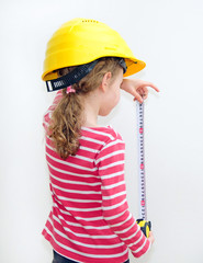 Little girl in hard hat measuring wall with tape measure.