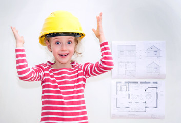 Little girl in hard hat standing near the wall with house plan.