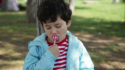 Young boy eating a lollipop at park and smiling