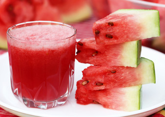 Watermelon juice with sliced fruit on white plate