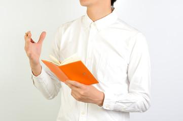 手帳でスケジュールを確認する白いシャツの男性