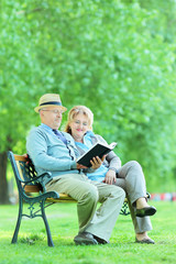 Mature couple reading a book in park