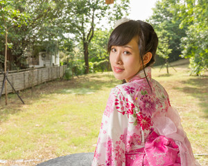 Asian woman wearing a kimono in Japanese garden