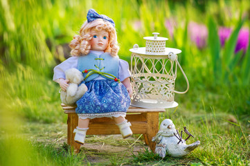 Still life in the spring garden with vintage collectible doll