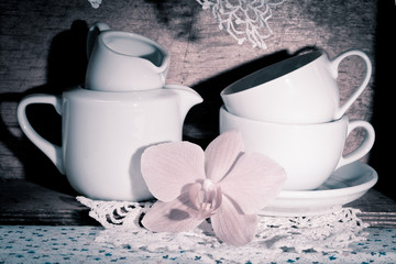 orchid and tableware placed on a wooden shelf