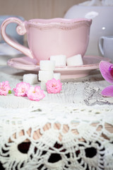 cup on wooden table with crochet doily