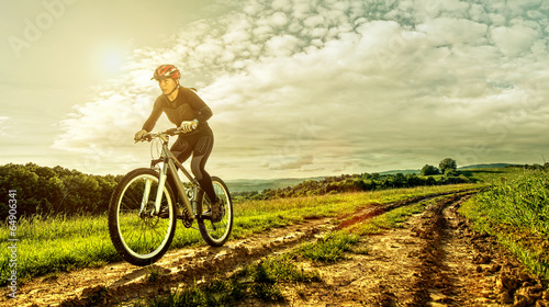 Plexiglas Wielersport Sport bike woman on a meadow with a beautiful landscape