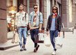 Three Young male fashion metraseksuals shop shopping walk