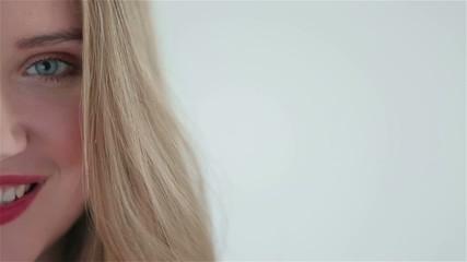 Beautiful blonde smiling woman's half face close up