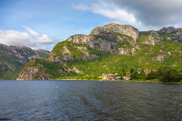 Norwegian landscape with houses and huts on the shore fjord.