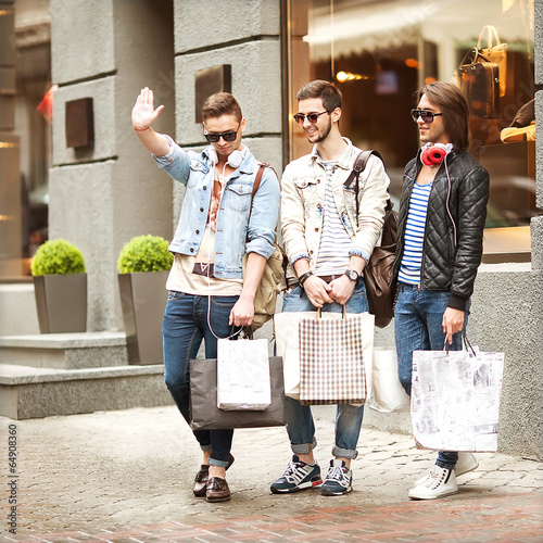 Fashion young guys go shopping with many colored shopping bags