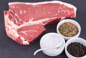 Raw T-bone steak and seasoning