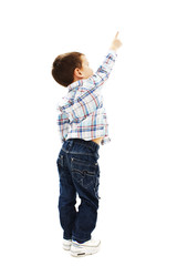 Back view of little boy points at wall. Rear view