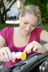 Frau füllt Scheibenreiniger in Auto nach
