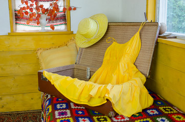 open suitcase with yellow  dress straw female hat