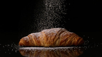 Powdered sugar sprinkling onto a croissant