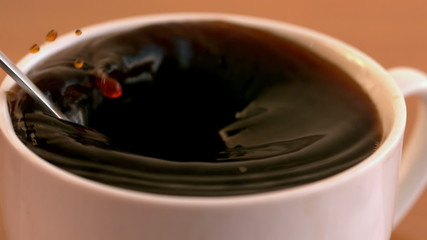 Teaspoon of sugar plunging into coffee cup