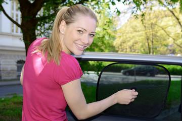 Frau befestigt Sonnenschutz an Auto-Fenster