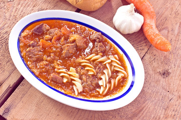 Beef stew with pasta on wooden background