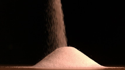 Sugar pouring on black background