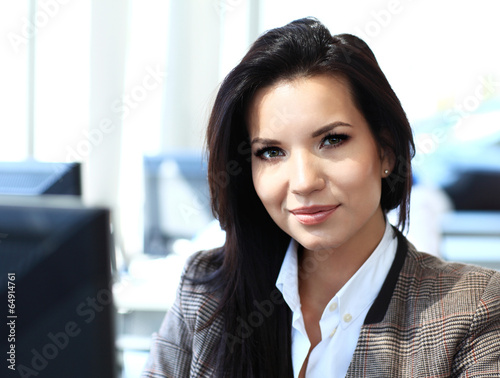 Casual businesswoman using laptop in office