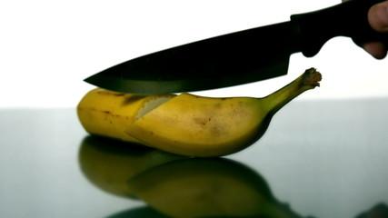 Man slicing banana with large knife