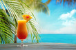 Refreshing orange cocktail on beach table. - 64915564