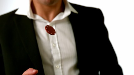 Man in suit flipping red casino chip