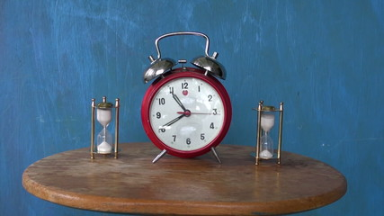 two sandglass and vintage alarm-clock on table