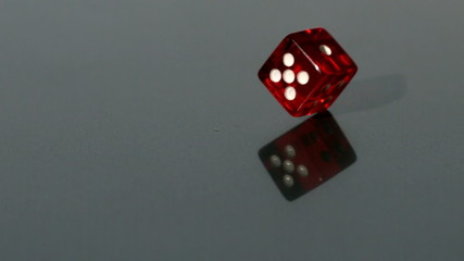 Red dice spinning on reflective surface