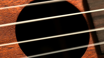 Hand strumming guitar strings close up