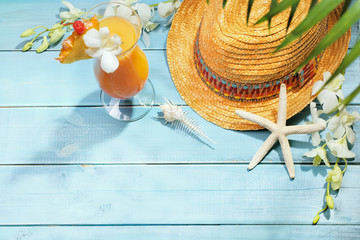 Straw hat and cocktail on wooden floor