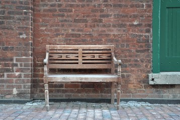 Wooden vintage chair in front of brick wall