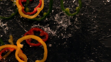 Pepper slices falling into water