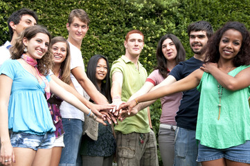 Group of teenagers with hands on stack