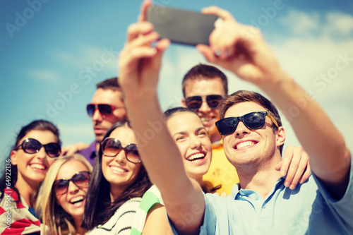 group of friends taking picture with smartphone - 64922136