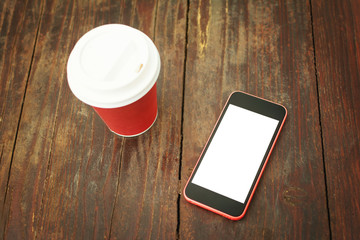 Smart phone and takeaway coffee cup on wooden table