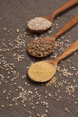 lentils, millet, oatmeal in a wooden spoon on the tablecloth