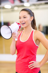 beautiful sporty woman with megaphone at gym