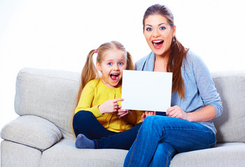 Mother with daughter sitting on sofa, hold white board.