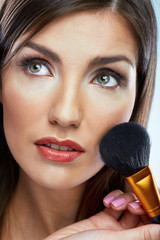 Beauty woman applying face make up with brush.