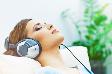 Portrait of resting young woman at home with listening music.