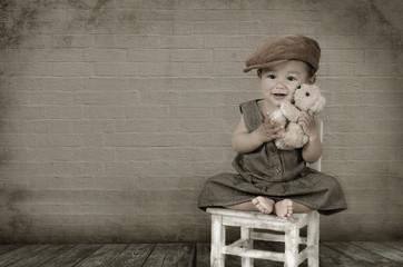 Kleines Mädchen mit Teddy sitzt auf einem Stuhl