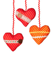 Three Handmade hearts with polka dots ribbons buttons on the whi