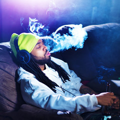 cool man smoking marijuana on his couch
