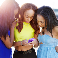 group of african girls looking at smart phone together