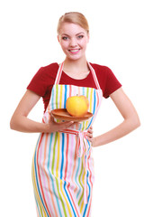 Happy housewife or chef in kitchen apron offering apple isolated
